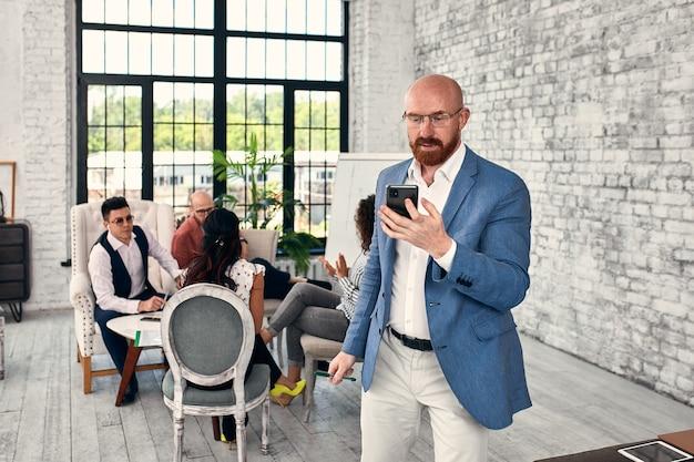Uomo di affari che ha una chiamata durante la riunione nella sala conferenze