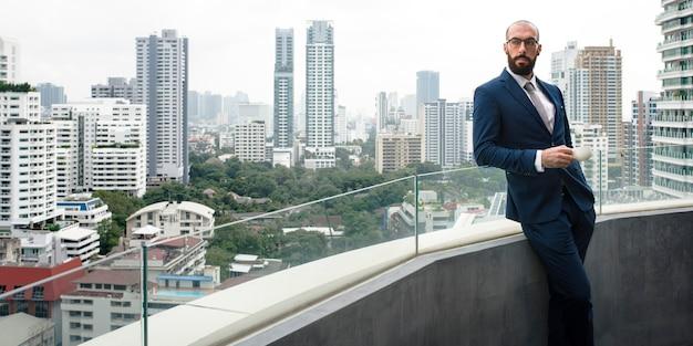 Uomo d'affari che fa una pausa caffè in un balcone con uno sfondo di paesaggio urbano