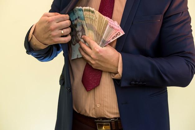 Uomo d'affari che nasconde il pacchetto dell'ucraina nella tasca della tuta. il concetto di corruzione e frode. uah 1000 nuove banconote in grivna