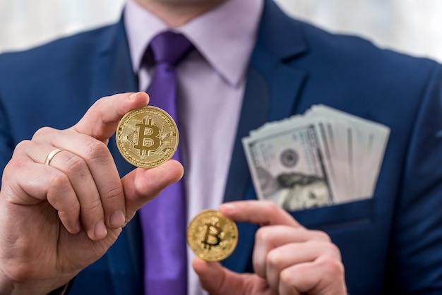 L'uomo d'affari tiene in mano dollaro e bitcoin