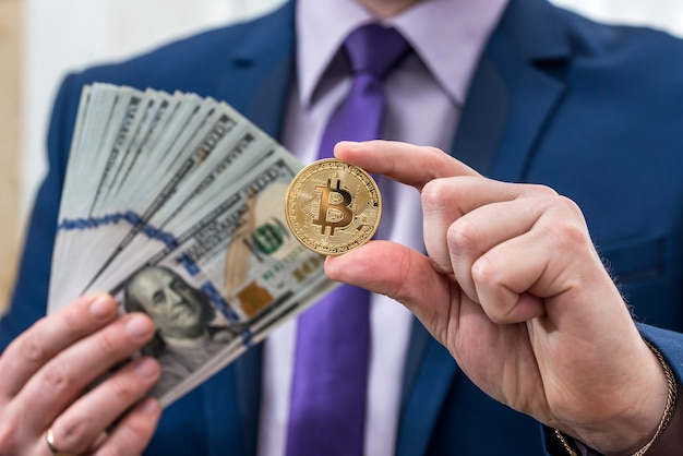 Uomo d'affari tenere in mano dollaro e bitcoin