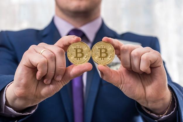 Uomo di affari che tiene in mano bitcoin