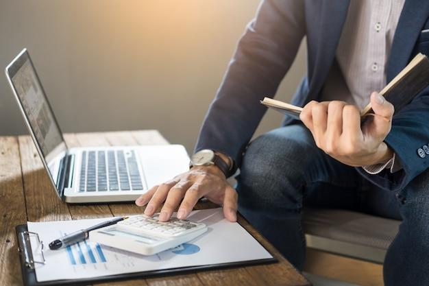 Uomo d'affari in possesso di un quaderno vuoto e calcolare business profitti business turnover con calcolatrice in caffè o cafe con un computer portatile