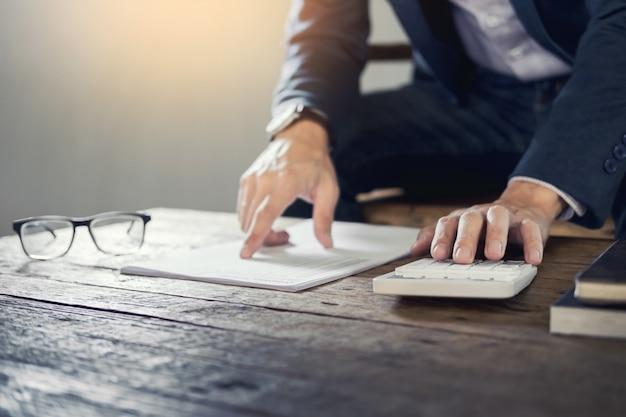 Uomo d'affari in possesso di un quaderno vuoto e calcolare affari affari fatturato con calcolatrice in caffè o caffetteria