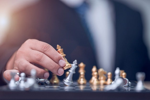 Uomo d'affari che tiene gli scacchi del re d'oro per finire il gioco