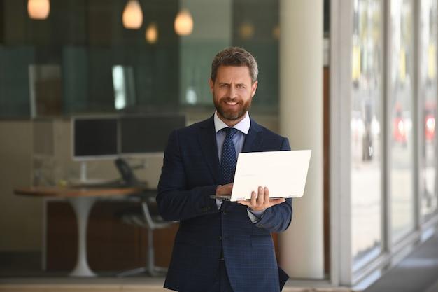Uomo d'affari che tiene il suo computer portatile in piedi in tuta sullo sfondo dell'ufficio
