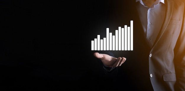L'uomo d'affari che tiene grafici olografici e statistiche del mercato azionario guadagna profitti. concetto di pianificazione della crescita e strategia aziendale. visualizzazione di uno schermo digitale di buona qualità.