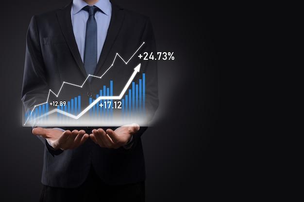 L'uomo di affari che tiene i grafici olografici e le statistiche del mercato azionario guadagna i profitti. concetto di pianificazione della crescita e strategia aziendale. visualizzazione di uno schermo digitale di buona qualità.