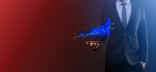 L'uomo d'affari che tiene grafici olografici e statistiche del mercato azionario guadagna profitti. concetto di pianificazione della crescita e strategia aziendale. visualizzazione di uno schermo digitale di buona qualità economica.