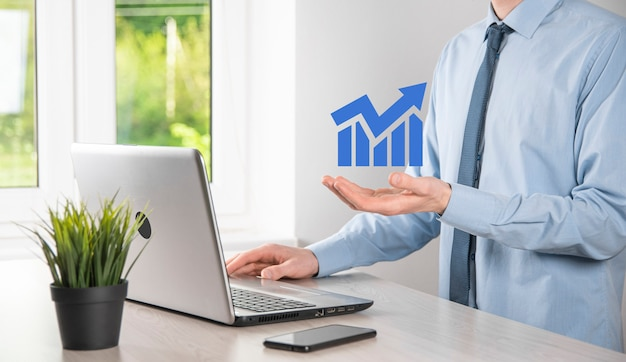 Uomo d'affari che tiene grafici olografici e statistiche del mercato azionario guadagnano profitti. concetto di pianificazione della crescita e strategia aziendale. visualizzazione di buona economia forma schermo digitale.