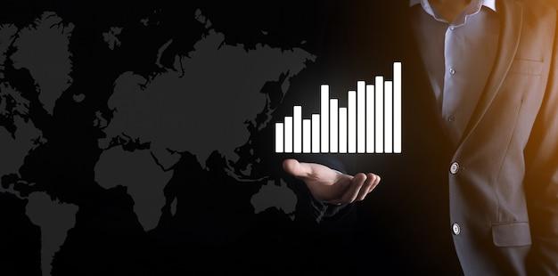 L'uomo d'affari che tiene grafici olografici e statistiche del mercato azionario guadagna profitti.