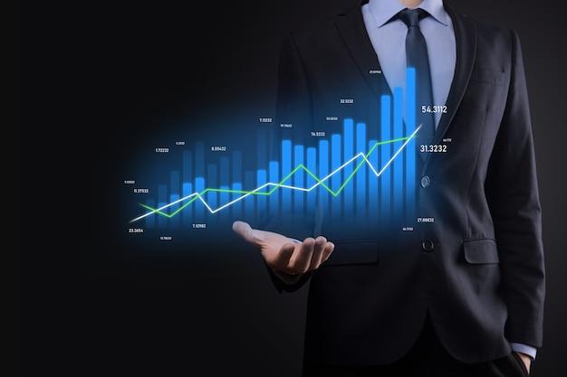 L'uomo d'affari che tiene grafici olografici e statistiche del mercato azionario guadagna profitti