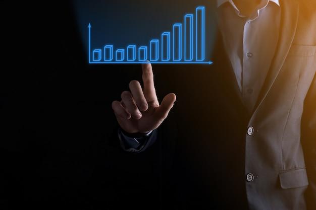 L'uomo di affari che tiene i grafici olografici e le statistiche del mercato azionario guadagna i profitti