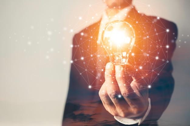 Uomo di affari che tiene una lampadina con i soldi delle monete e lo spazio della copia per contabilità, idee e concetto creativo.