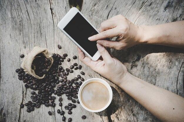 Albero della tazza del telefono e di caffè della tenuta dell'uomo di affari in uno