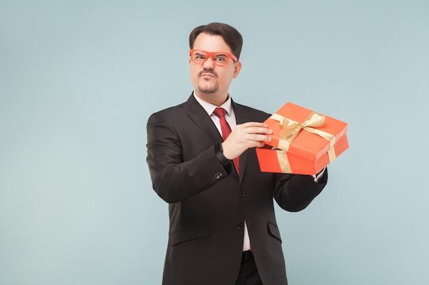 Uomo d'affari che tiene in mano una confezione regalo rossa deluso dal regalo