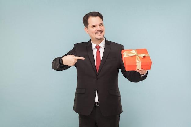Uomo d'affari che tiene il dito puntato in una scatola regalo rossa