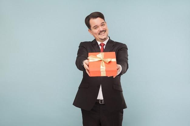 Uomo d'affari che tiene una scatola regalo rossa presente per te