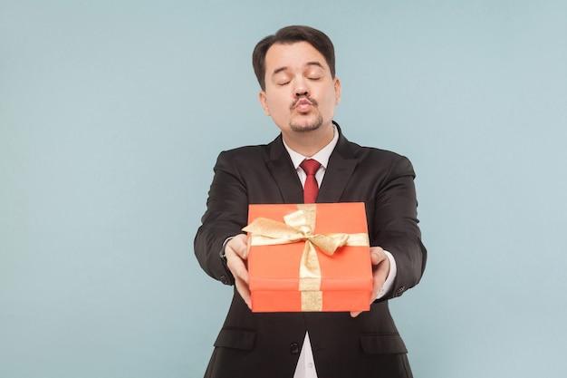 L'uomo d'affari che tiene in mano una scatola regalo rossa manda un bacio d'aria
