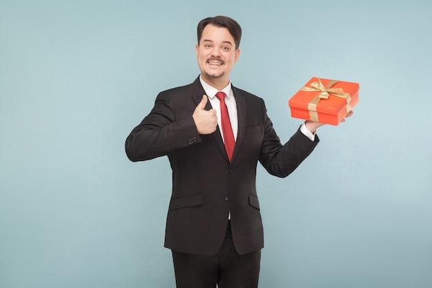 Uomo d'affari che tiene in mano una scatola regalo rossa che mostra un segno simile