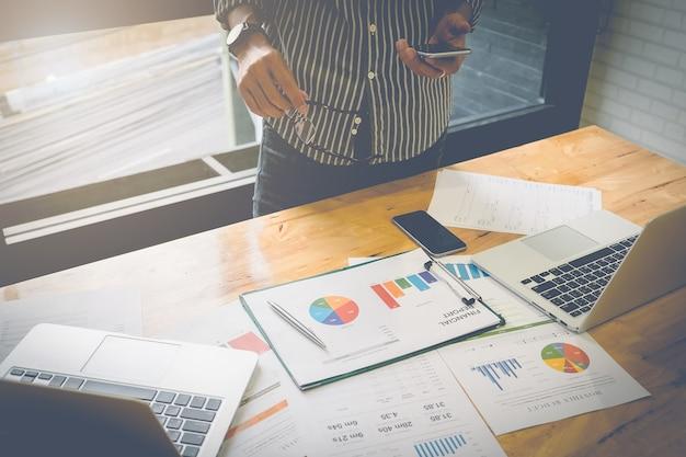 Uomo d'affari in possesso di smartphone e scrivendo lavoro di carta finanziaria e computer portatile sulla scrivania in legno ufficio interno con luce di mattina. effetto del filtro dell'annata.