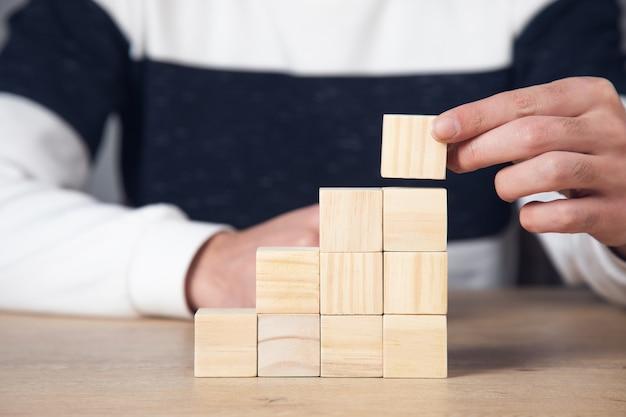 Uomo di affari che tiene i cubi di legno sulla tavola