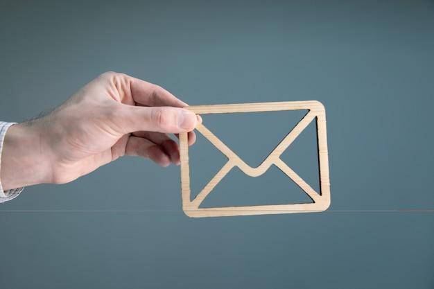 Uomo d & # 39; affari che tiene segno di lettera in legno