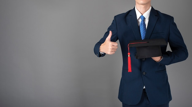 L'uomo di affari sta tenendo il cappello di graduazione, concetto di istruzione di affari