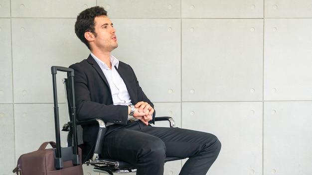 L'uomo d'affari è seduto su una sedia in attesa di un viaggio d'affari con la valigia e guardando la lancetta dell'orologio.