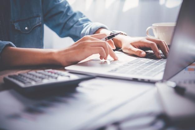 L'uomo d'affari è seduto su un laptop sulla scrivania dell'ufficio. analisi e pianificazione del concetto di business