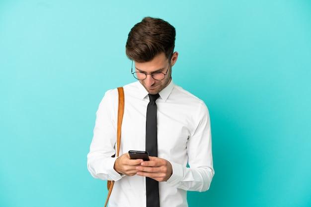 Uomo d'affari su sfondo isolato inviando un messaggio con il cellulare