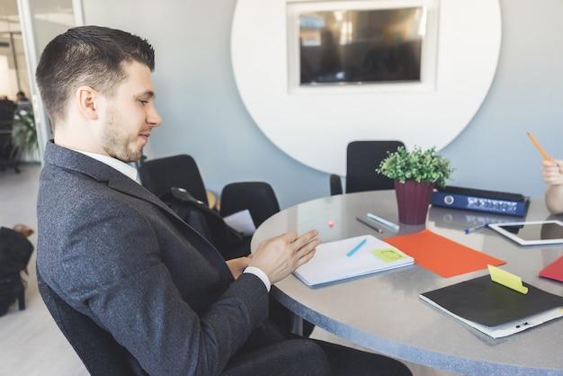 Un uomo d'affari in giacca è seduto alla scrivania al lavoro in ufficio. vista laterale