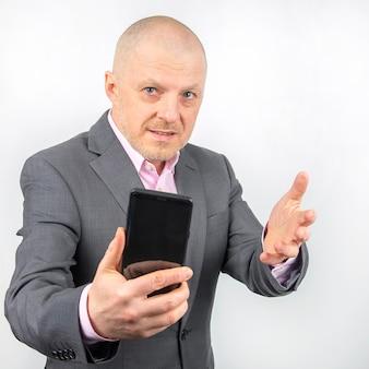 Uomo d'affari in una giacca con un telefono cellulare in mano su uno sfondo chiaro