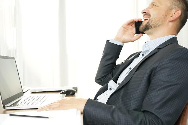Uomo d'affari, appoggiato allo schienale della sedia, parlando al telefono, sorridente e felice