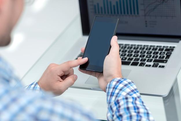 Uomo d'affari guardando lo schermo del suo smartphone