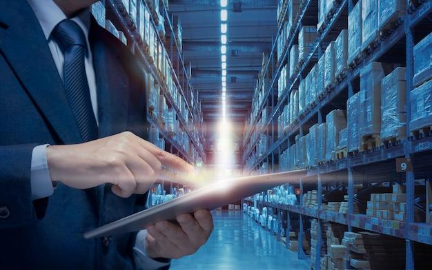 L'uomo d'affari gestisce il magazzino tramite internet spettacolo di tecnologia magazzino moderno, concetto di business di rete di distribuzione. l'uomo d'affari usa il tablet per pianificare, controllare, controllare il trasporto logistico in magazzino