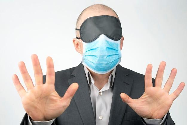 Uomo d'affari in una maschera medica e benda sugli occhi per dormire con le mani in alto su un bianco