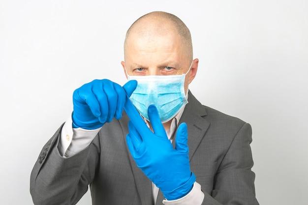 L'uomo d'affari in una mascherina medica si toglie i guanti protettivi dalle mani. quarantena del virus
