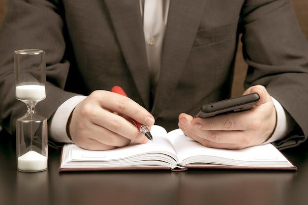 L'uomo d'affari in ufficio sta lavorando con un telefono cellulare nello spazio di una clessidra. obiettivo aziendale e di successo