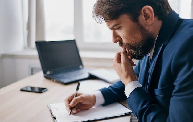 Un uomo d'affari in ufficio al tavolo scrive documenti informativi un laptop in background. foto di alta qualità