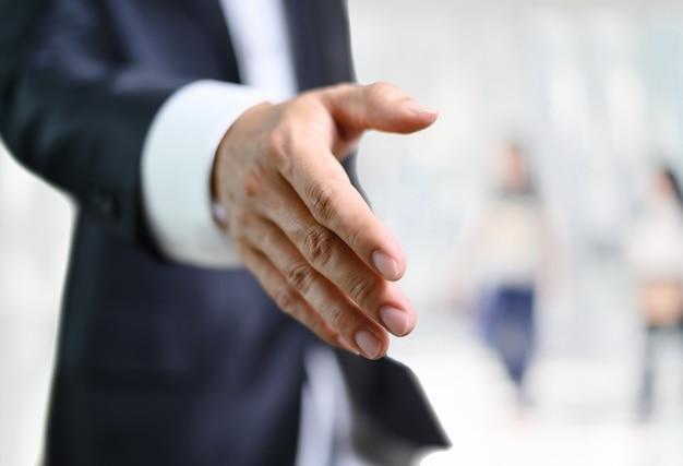 La mano aperta dell'uomo di affari pronta per sigillare un affare, partner che stringe le mani