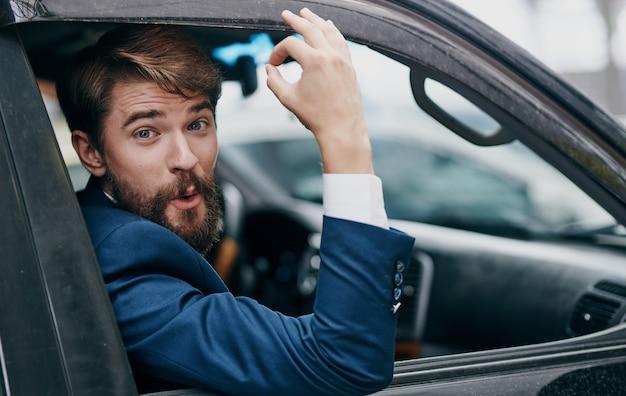 Uomo di affari che dà una occhiata dal professionista di viaggio del finestrino dell'auto.