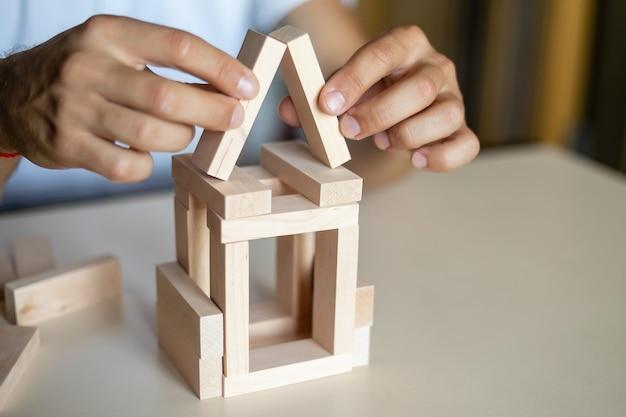 Uomo d'affari posizionando un blocco di legno su una torre di controllo del rischio concetto di rischio alternativo