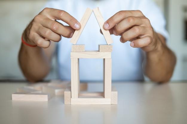 Uomo d'affari che posiziona un blocco di legno su un controllo del rischio di concetto di torre, pianificazione e strategia negli affari. concetto di rischio alternativo, rischio di creare un concetto di crescita aziendale con blocchi di legno