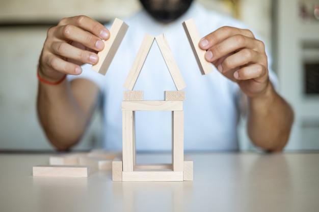 Uomo d'affari che posiziona un blocco di legno su un concetto di torre di controllo del rischio, rischio di creare un concetto di crescita aziendale con blocchi di legno