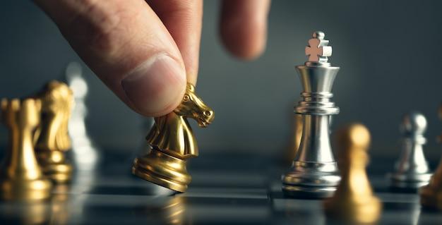 Uomo di affari che gioca scacchi isolato sul nero