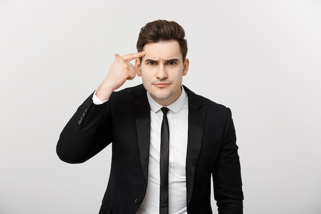 L'uomo d'affari punta il dito alla testa e pensa isolato su uno sfondo grigio