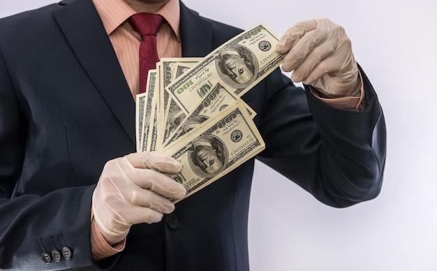 Uomo d'affari in guanti protettivi con denaro isolato su sfondo bianco. concetto medico covid 19 coronavirus