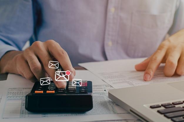 Un uomo d'affari che legge una lettera in sospeso da un contribuente e annota il calcolo del calcolatore delle tasse annuale per prevenire e bloccare le e-mail di spam da internet