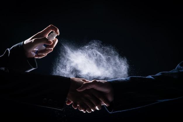 L'uomo d'affari stringe la mano a suit donna e spruzza alcol disinfettante al 70% per uccidere coronavirus o covid-19 prima di agitare, nuovo normale concetto di stile di vita aziendale, bassa esposizione scura